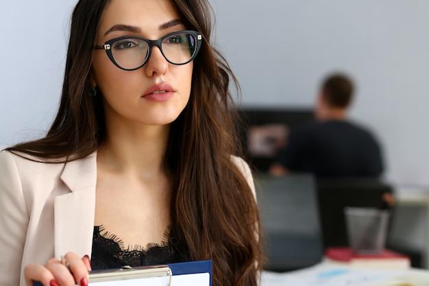 Biznes kobieta w beżowym kolorze z okularami, trzymając dokumenty