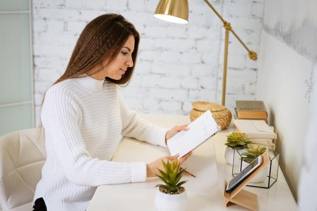 Biznes kobieta w białym swetrze pisze w zeszycie siedząc przy stole