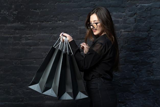 Biznes kobieta w czarne ubrania z czarnymi torby na zakupy na ciemnym tle. czarny piątek.