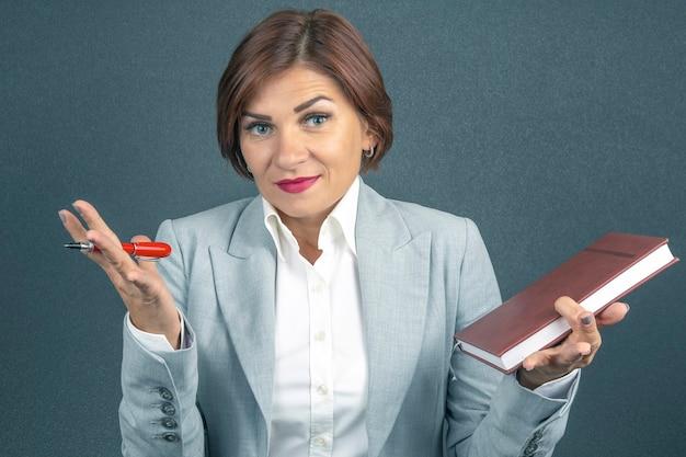 Biznes kobieta w garniturze z piórem i notatnikiem w ręce. determinacja i rozwój kariery