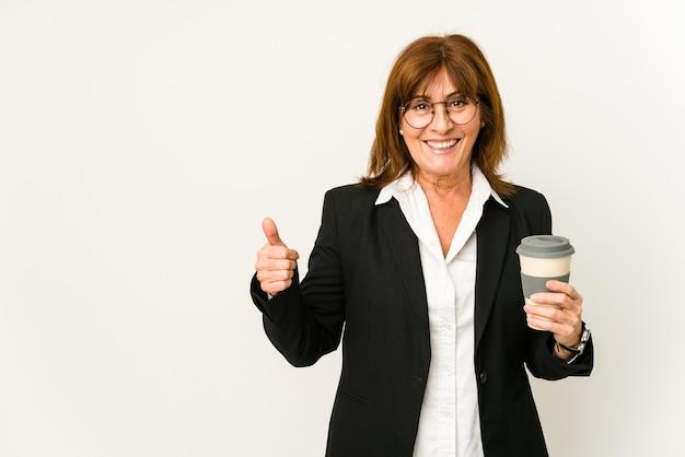 Biznes kobieta w średnim wieku trzyma kawę na wynos na białym tle uśmiechnięty i podnoszący kciuk do góry