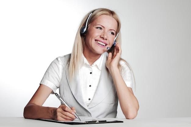 Biznes kobieta w zestawie słuchawkowym, pisząc w notesie