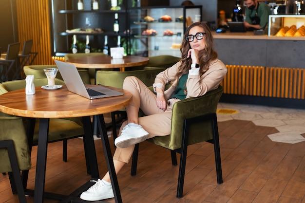 Biznes kobieta właściciel restauracji używać laptopa ubrana eleganckie spodnie siedzi stół w restauracji z barem tło kaukaski kobieta biznesmen kryty pełnej długości