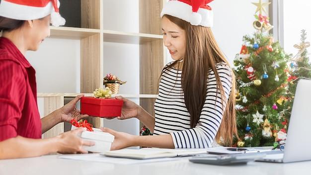 Biznes kobieta wymiany prezentu w biurze w ostatnim dniu roboczym. młodzi kreatywni ludzie świętują wakacje w nowoczesnym biurze.