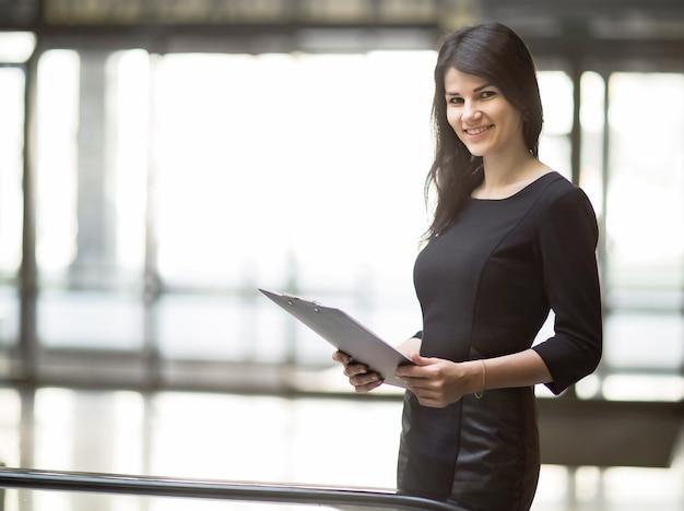 Biznes kobieta z dokumentami na tle przestronnego biura