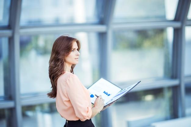 Biznes kobieta z dokumentów finansowych stojących w pobliżu dużego okna w biurze