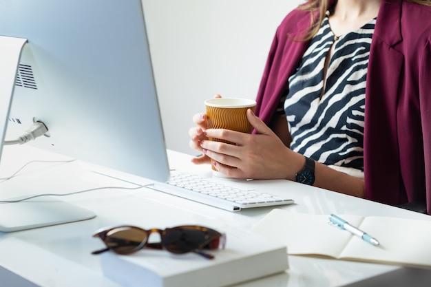 Biznes kobieta z filiżanką kawy przy biurku w minimalistycznym biurze. młoda osoba płci żeńskiej przed komputerem stacjonarnym w nowoczesnym miejscu pracy