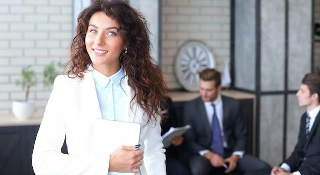 Biznes kobieta z jej personelem, grupa ludzi w tle w nowoczesnym, jasnym biurze w pomieszczeniu.
