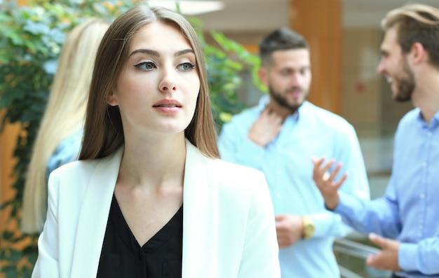 Biznes kobieta z jej personelem, grupa ludzi w tle w nowoczesnym, jasnym biurze.