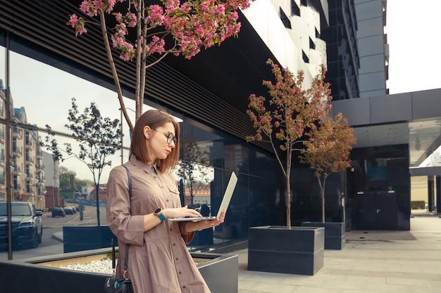Biznes kobieta z komputerem na tle nowoczesnego budynku firmy.