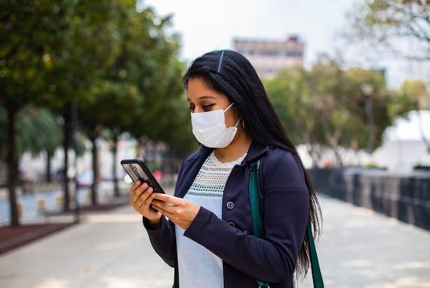 Biznes kobieta z maską, która stoi, wpisując swój telefon