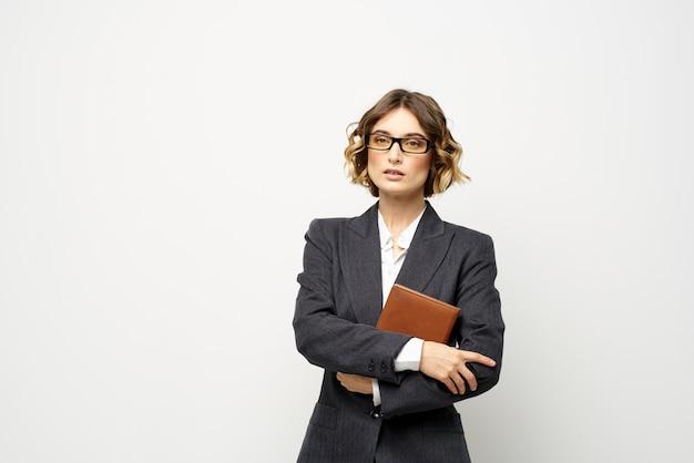 Biznes kobieta z notatnikiem i okularami pracy światła przycięty widok modelu garnituru.