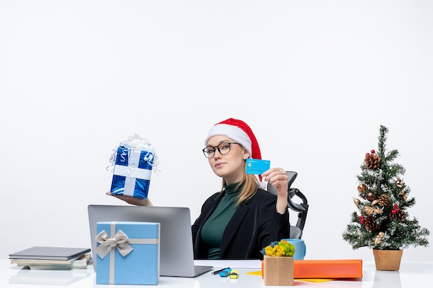 Biznes kobieta z santa claus kapelusz i noszenie okularów siedzi przy stole trzymając prezent na boże narodzenie i kartę bankową w biurze