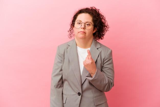 Biznes kobieta z zespołem downa na białym tle na różowej ścianie, wskazując palcem na ciebie, jakby zapraszając, podejdź bliżej.