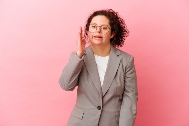 Biznes kobieta z zespołem downa na białym tle na różowym tle krzycząc i trzymając dłoń w pobliżu otwartych ust.
