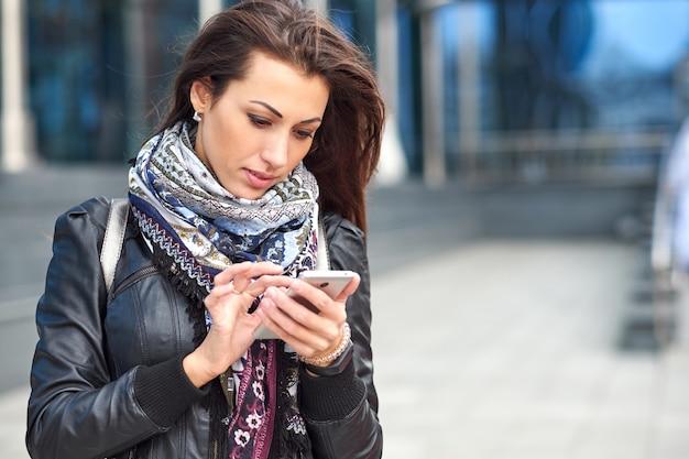 Biznes kobieta za pomocą inteligentnego telefonu na tle biurowca.