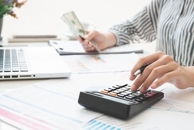 Biznes kobieta za pomocą kalkulatora i pisania notatek z obliczenia. podatki i koncepcje ekonomiczne.