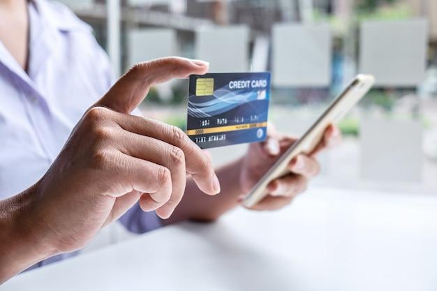 Biznes kobieta za pomocą smartfona, laptopa i trzymając kartę kredytową do płacenia szczegółów strony wyświetlają zakupy online i kod zabezpieczający wpis do wprowadzania informacji o karcie.