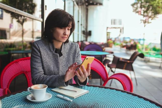 Biznes kobieta za pomocą żółtego samrtphone i robienia notatek