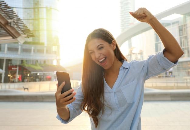 Biznes kobieta zaczyna dzień od dobrych wiadomości na swoim smartfonie