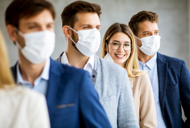 Biznes kobieta zdejmując ochronną maseczkę na twarz z członkami jej zespołu stojącymi w kolejce w biurze