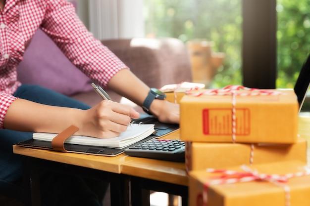 Biznes kobieta ze sprzedażą online i wysyłką paczek w swoim biurze domowym.