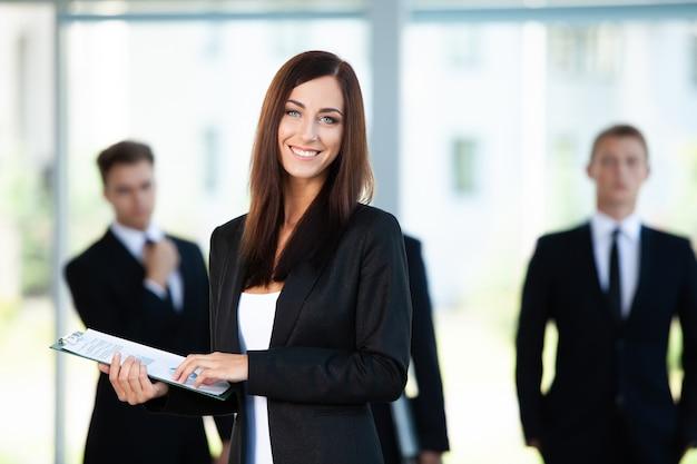 Biznes kobieta ze swoim personelem, grupa ludzi w tle w nowoczesnym pomieszczeniu jasny biuro.
