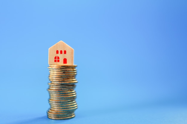 Biznes, kredyt hipoteczny, koncepcja kredytu mieszkaniowego. zbliżenie drewniany blok na szczycie stosu złotych monet na niebiesko z miejsca na kopię.