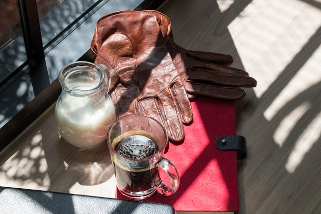 Biznes książka sukces, dzbanek mleka, brązowe skórzane rękawiczki i czarną kawę na drewno.