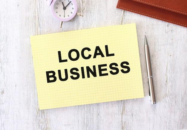 Biznes lokalny tekst zapisany w notatniku leżącym na drewnianym stole roboczym. pomysł na biznes.