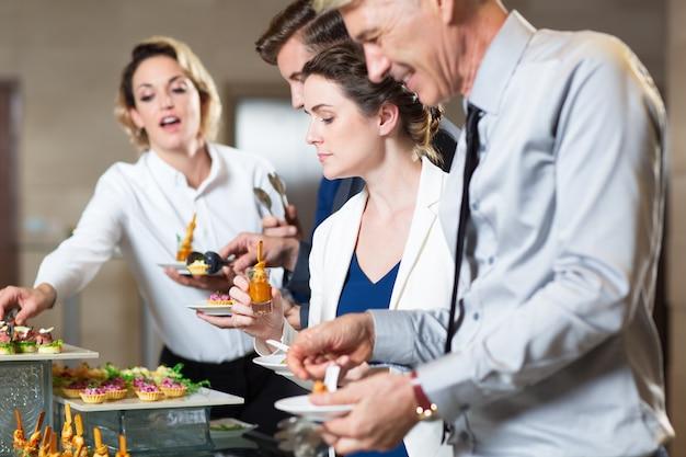 Biznes ludzie służenia sobie samemu z przekąskami