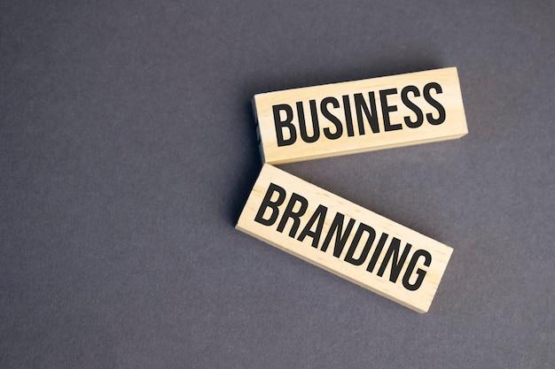 Biznes marki słowa na drewnianych klockach na żółtym tle. koncepcja etyki biznesu.