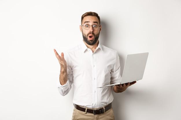 Biznes. mężczyzna trzymający laptopa i wyglądający na zdumionego, zaskoczonego stroną internetową, stoi