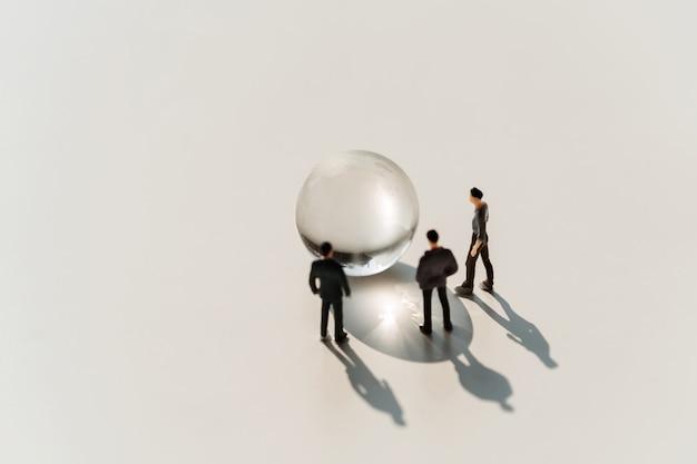 Biznes miniatury zabawka z kuli ziemskiej szkłem na białym tle