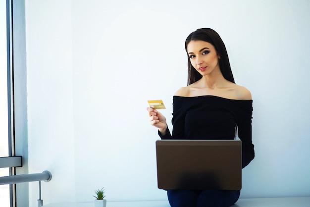 Biznes. młoda biznesowa kobieta trzyma kredytową kartę w rękach. siedzi na stole w big light office i pracuje na komputerze. praca w domu. wysoka rozdzielczość