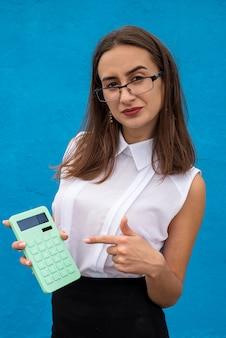 Biznes młoda dama z zielonym kalkulatorem na białym tle na niebieskiej ścianie. pojęcie finansów