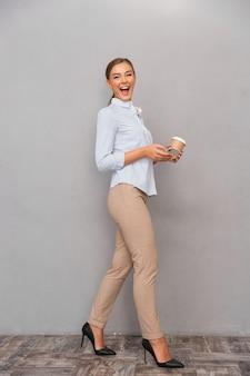 Biznes młoda kobieta pozowanie na białym tle nad szarym tle ściany za pomocą telefonu komórkowego picia kawy.