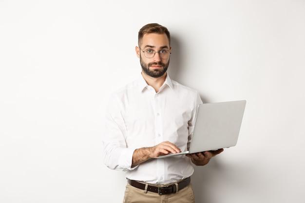Biznes. młody przystojny biznesmen pracuje na laptopie, wykonuje pracę na komputerze, na stojąco