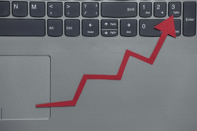 Biznes online, handel. klawiatura laptopa z czerwoną strzałką wzrostu. wykres strzałki w górę.