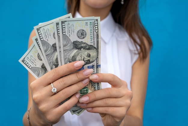 Biznes pani trzyma wiele dolarów na białym tle na niebieskim tle. koncepcja finansowa