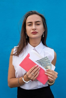 Biznes pani w kajdankach trzyma kopertę z dolarami. koncepcja przekupstwa i korupcji