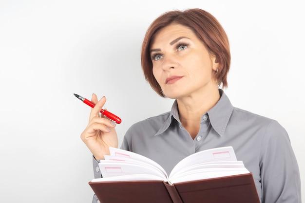 Biznes pani z piórem i dokumentów w jej rękach na białym tle