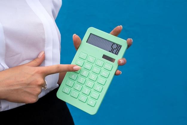 Biznes panienka z zielonym kalkulatorem na białym tle na niebieskim tle. pojęcie finansów