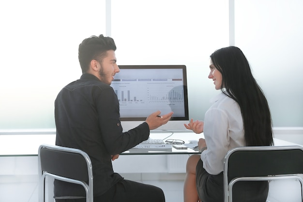Biznes para omawianie danych finansowych, siedząc przy komputerze stacjonarnym