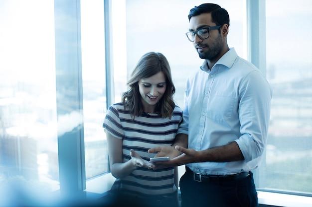 Biznes para przy użyciu telefonu komórkowego przed szklanym oknem