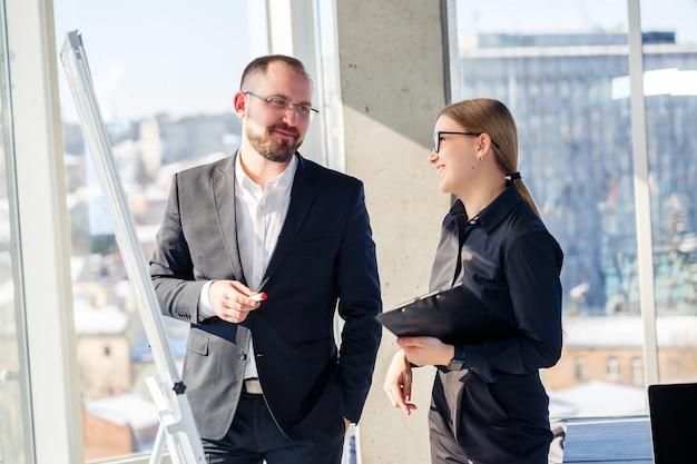 Biznes para rozmawia o czymś stojąc w biurze. partnerzy biznesowi rozmawiają o nowym projekcie