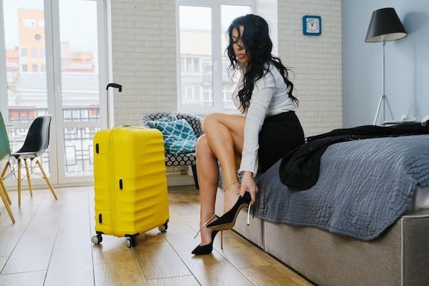 Biznes piękna kobieta siedzi na łóżku w hotelu, zmęczona po podróży służbowej kobieta zdejmując buty, walizka wnętrza mieszkania w tle