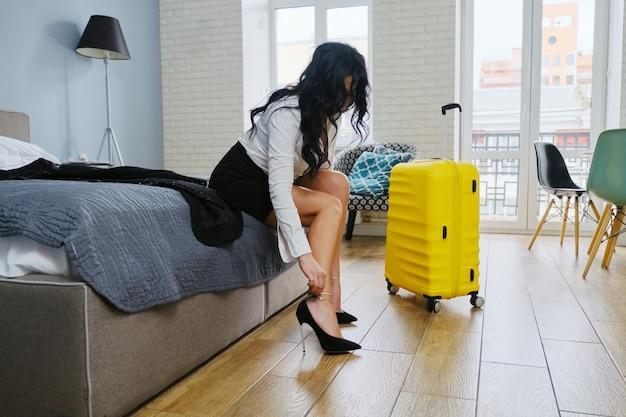Biznes piękna kobieta siedzi na łóżku w hotelu, zmęczony po podróży służbowej