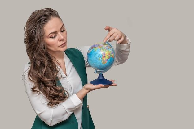 Biznes piękna kobieta z kulą ziemską w dłoniach wskazuje punkt na świecie.