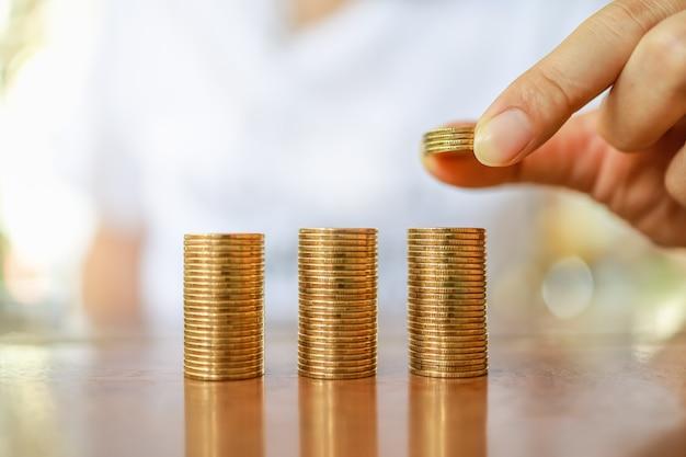 Biznes, pieniądze, finanse, oszczędzanie i bezpieczna koncepcja. zamyka up mężczyzna ręki mienie i stawia cztery monety brogować monety na drewnianym stole.